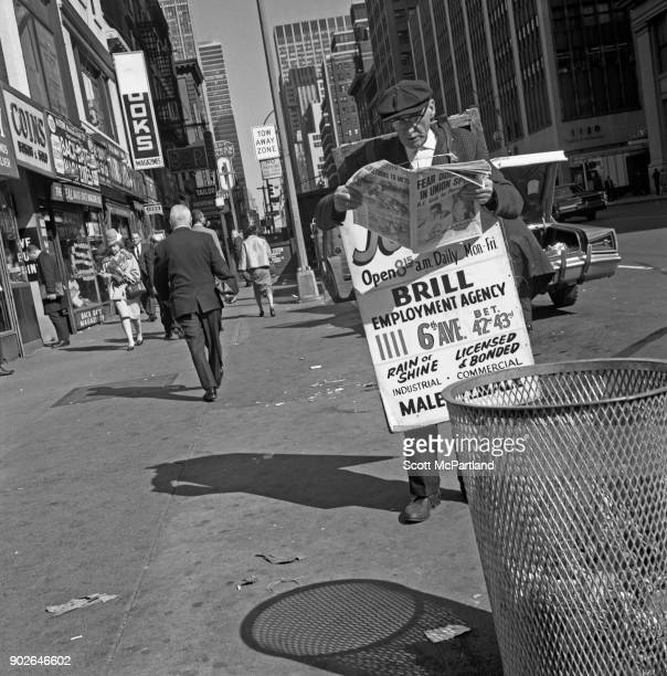 A man wearing a billboard advertisement reads the news paper on 42nd street in Times Square New York