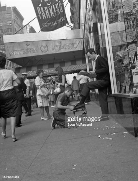 A young boy shines a man's shoes as he reads the papers on Seventh avenue in front of the Sheraton hotel in Times Square New York