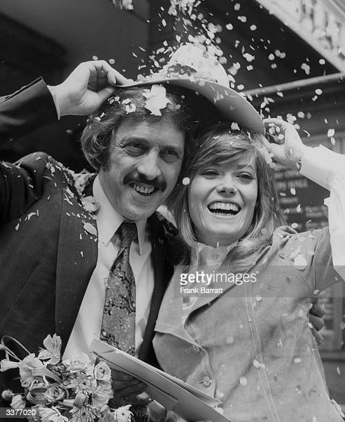 British actress Wendy Richard and her groom London businessman Leonard Black share a hat to shelter from confetti at their wedding at Caxton Hall