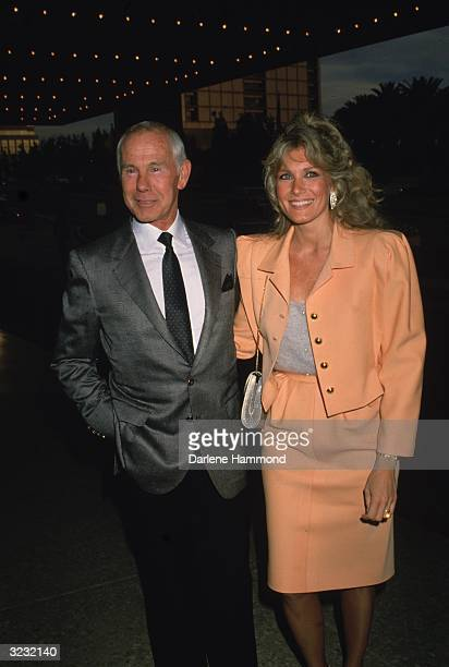 American talk show host Johnny Carson standing with his fourth wife Alexis under a theater marquee at the opening of the musical 'Les Miserables'...