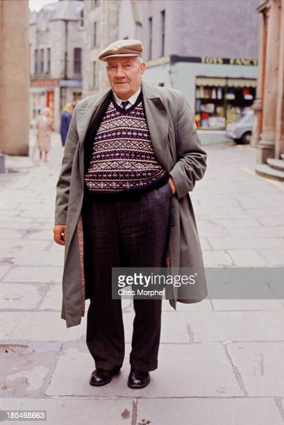 A man poses wearing a Fair Isle sweater and overcoat in Lerwick Shetland Islands in June 1970