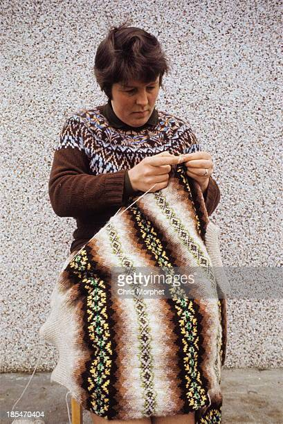 A woman poses wearing a Fair Isle jumper while knitting another Fair Isle jumper in front of the wall of a cottage on one of the Shetland Islands in...