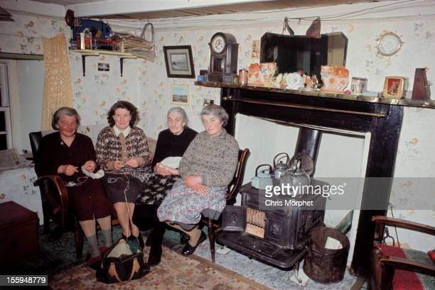 Four elderly women two of whom are knitting pose in the living room of a cottage on one of the Shetland Islands in June 1970