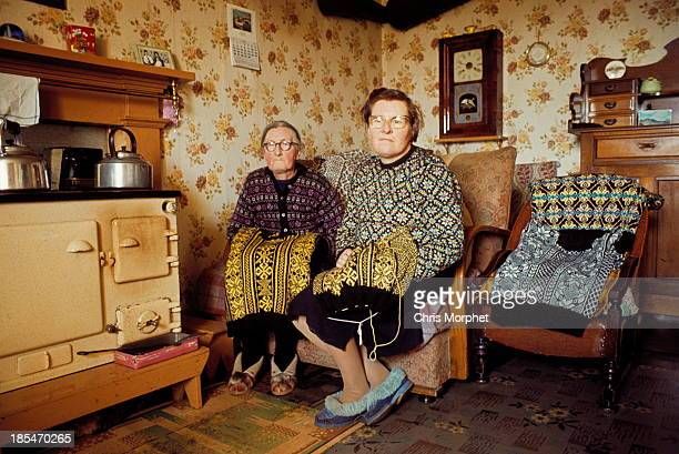 Two elderly women knitting Fair Isle style jumpers pose in the living room of a cottage on one of the Shetland Islands in June 1970