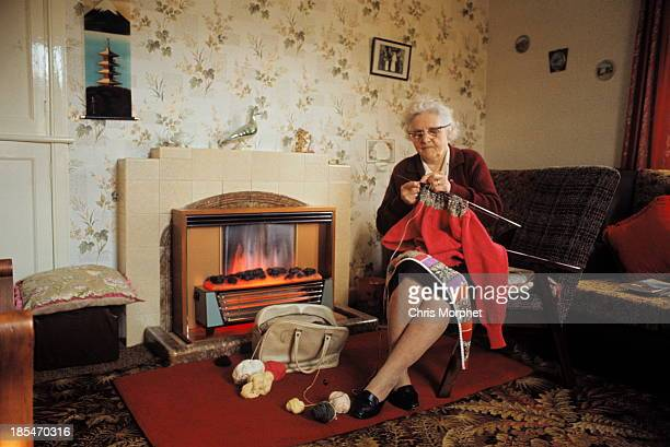 View of an elderly woman knitting a Fair Isle style jumper by a gas fire in the living room of a cottage on one of the Shetland Islands in June 1970