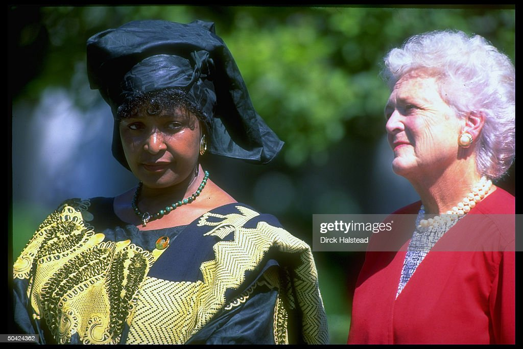 1st Lady Barbara Bush (R) & S. African ANC ldr.'s wife Winnie Mandela listening to their husbands speak at arrival fete on WH grounds.