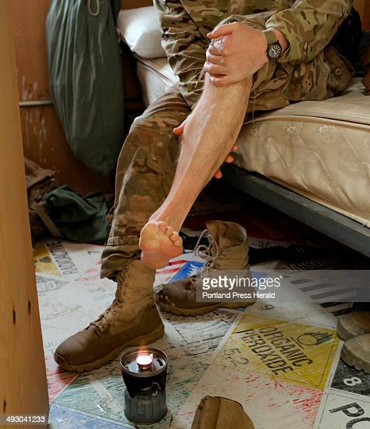 1st Lt Dan Landers of the 133rd Engineer Battalion of the Maine Army National Guard takes a break Monday December 30 to heat his feet by an open...