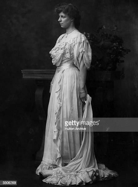 Miss Symes Thompson wearing an elegant silk evening dress and carrying threequarter length gloves