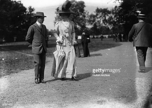 Lady de Bathe formerly Lillie Langtry takes a walk in the park with a companion