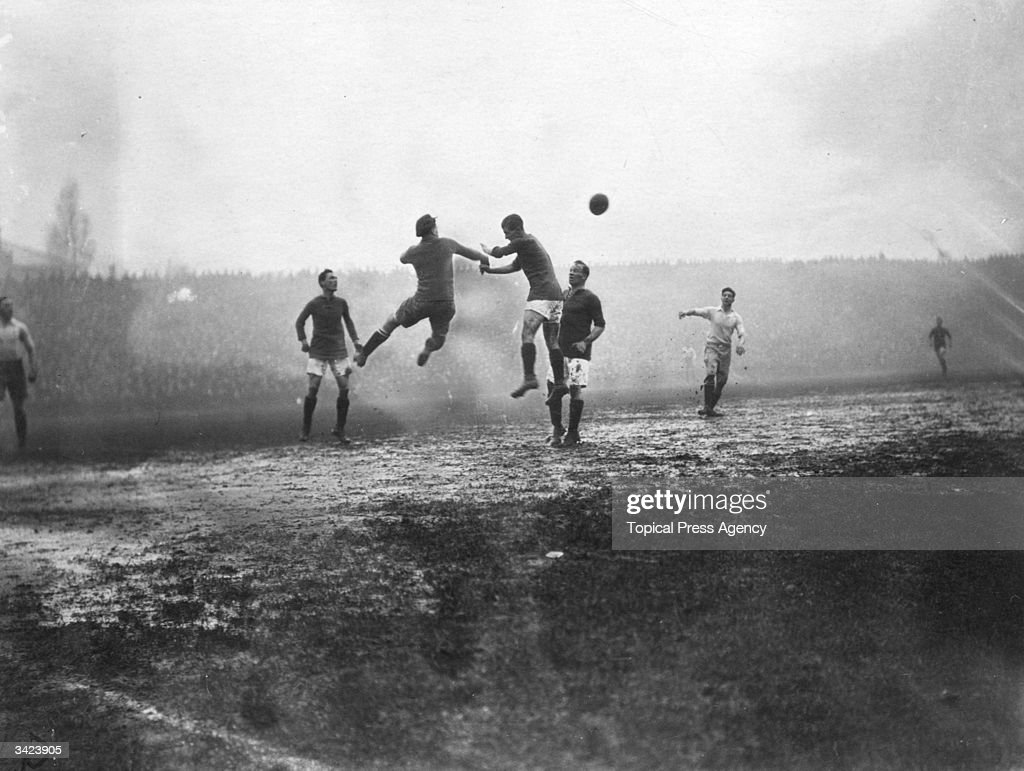 Players jump for the ball in a match between Arsenal and Preston North End at Highbury, London.