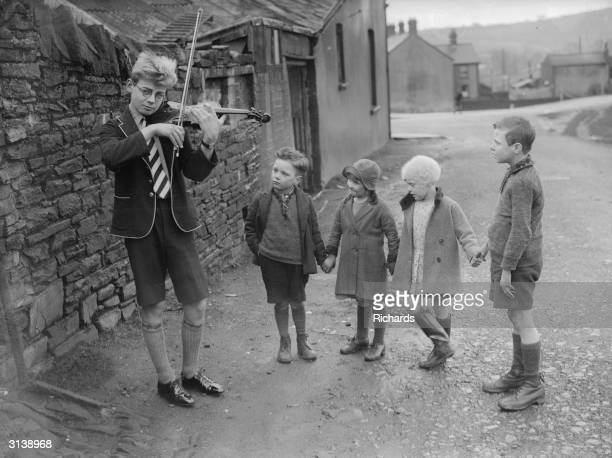 Thirteen year old Merriville Davey of Thomastown Glamorgan playing the violin in the village street to a small group of young villagers He came...