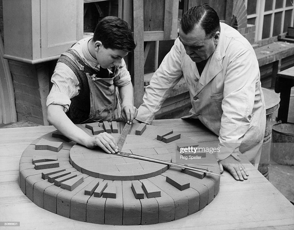 A pupil at the LCC School of Building at Brixton, London finishing off a clock made of bricks made for the school exhibition.