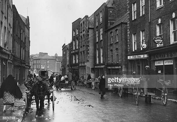 Market day in the city of Limerick County Limerick Ireland The man on the right is driving a horse and trap the typical transport of the better off...