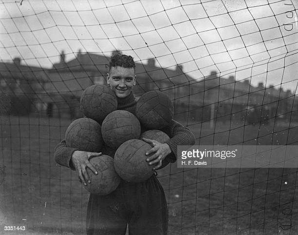 Tottenham Hotspur's goalkeeper Percy Hooper holds an arm full of footballs during a training session