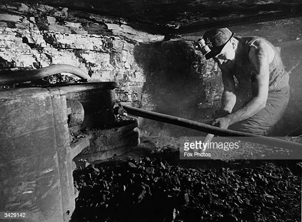 Crouched in a cramped shaft a coal miner hacks at the coalface at Ashington Colliery in Northumberland