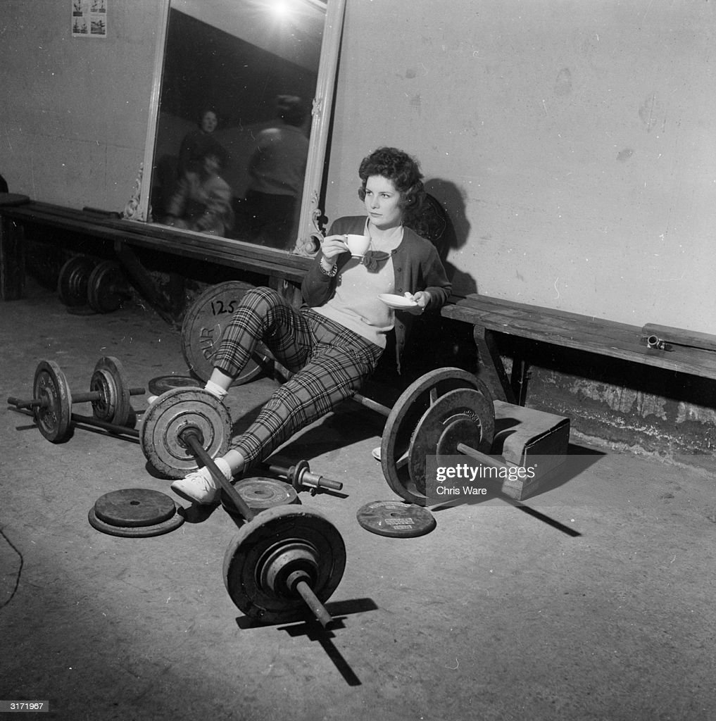 Valerie Barker has a tea break after a weight-training session at a gymnasium in a renovated air-raid shelter in South Oxley, near Watford, Hertfordshire. The gym is run by former submariner, Vivian Bentley, who claims his training regime improves the figure and posture.