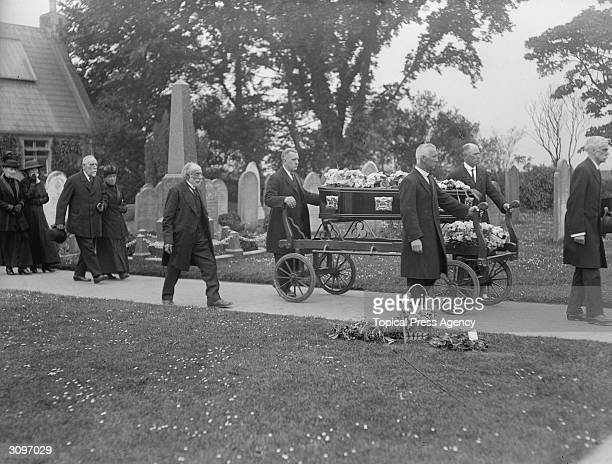 A coffin at the funeral of Folkestone airraid victims is wheeled through a graveyard on a trolley