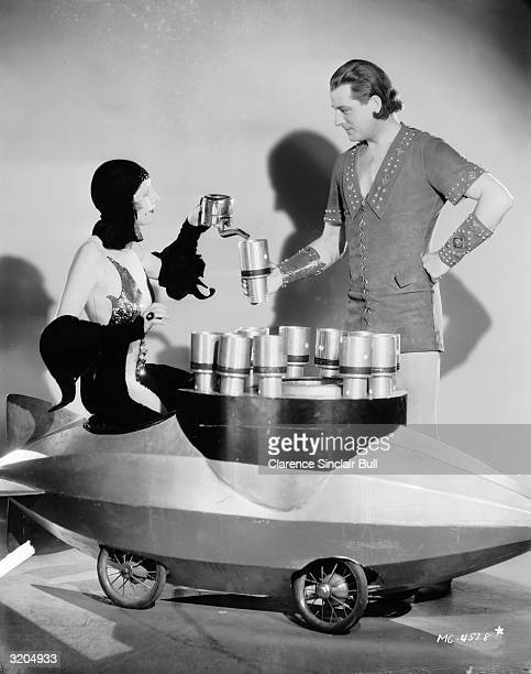 Kay Johnson serves tea to Reginald Denny from a trolley shaped like a dirigible in a scene from 'Madame Satan', directed by Cecil B DeMille.