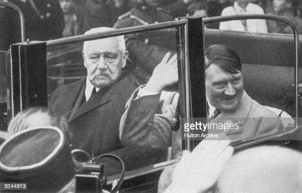 Reich President Paul von Hindenburg and Nazi leader Adolf Hitler the newly appointed Chancellor of Germany ride in an open car during a parade Germany