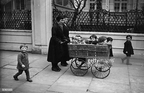 Youngsters from St Margaret Day Nursery at Battersea are taken out in a basket on a pram during the bus strike