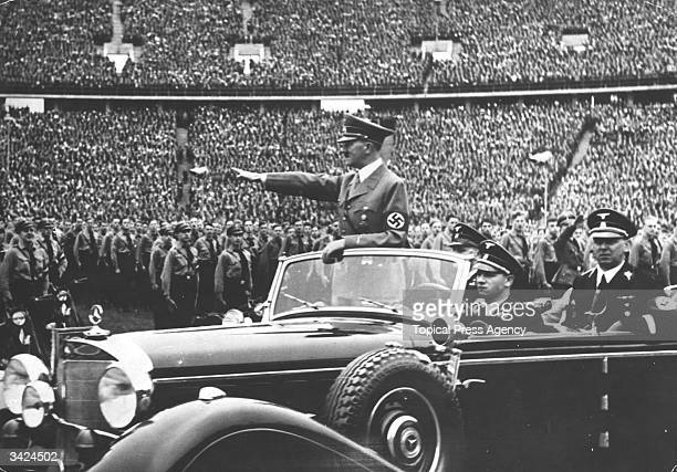 Adolf Hitler the German dictator giving a nazi salute to a crowd of soldiers at a nazi rally
