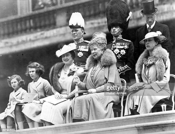 Queen Elizabeth Queen Consort to King George VI with Queen Mary and the Royal Princesses Elizabeth and Margaret Rose watching the presentation of new...