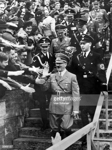 Adolf Hitler, Fuehrer of Germany's Third Reich, enjoying an ecstatic reception at the Olympic Stadium, Berlin, as he arrives to address 132,000...