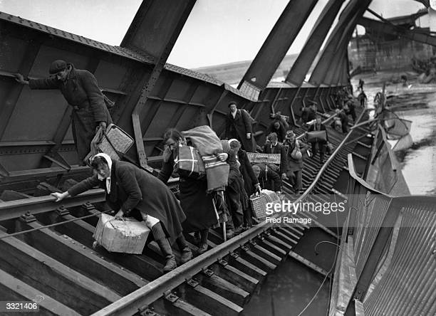 Displaced Persons crossing a bridge on the River Elbe at Tangermunde which has been blown up by the Germans to escape the chaos behind German lines...