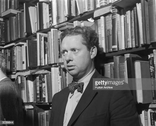 Welsh author Dylan Thomas standing in front of a bookshelf at the Gotham Book Shop during a reception held in his honor New York City