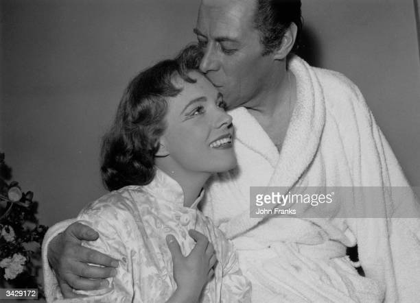 Star of the musical 'My Fair Lady' Rex Harrison gives his costar Julie Andrews a kiss backstage in her dressingroom after the show at the Drury Lane...