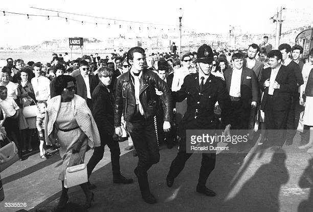 A policeman escorts a teenager after violence between Mods and Rockers in Margate Kent