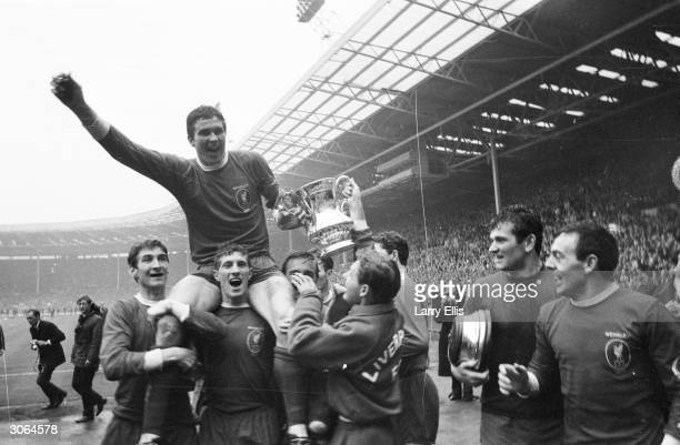 Captain of Liverpool FC Ron Yeats holds the FA cup as he is chaired by fellow members of the victorious team Ian St John is on the far right