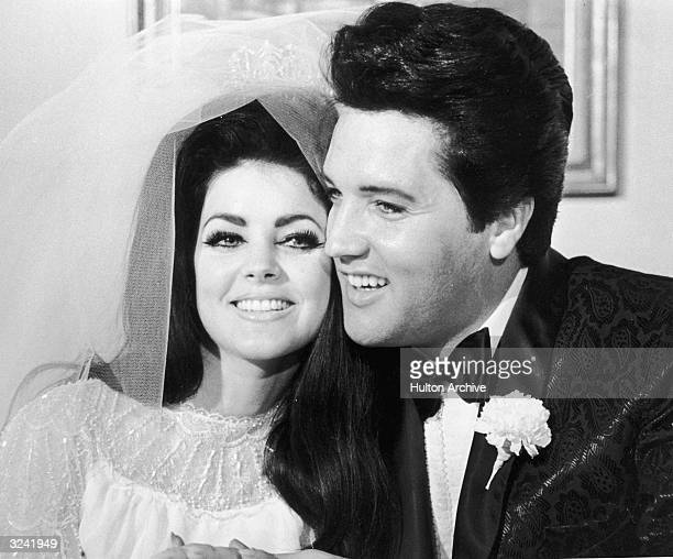 American rock musician Elvis Presley and his wife Priscilla Beaulieu Presley hugging each other on their wedding day Las Vegas Nevada Priscilla wears...