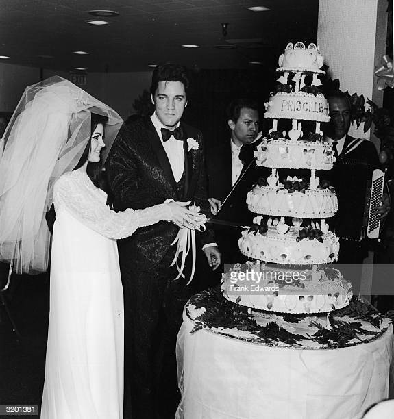 American rock n' roll singer Elvis Presley cuts his wedding cake with his wife Priscilla Beaulieu Presley at their wedding reception Las Vegas Nevada