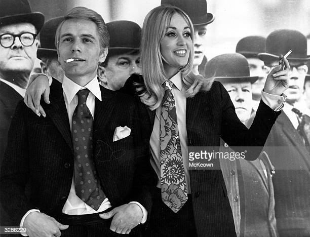 Pop singer and actor Adam Faith and his wife model Jackie Irving wearing 'his and her' suits and ties in front of a backdrop of city gents