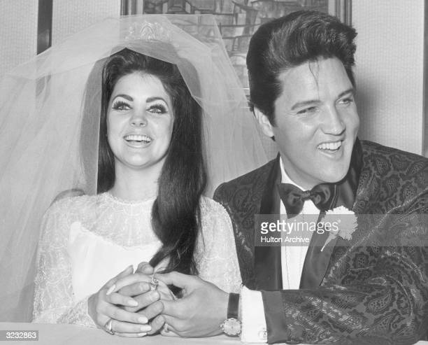 Rock and roll singer and actor Elvis Presley holding hands with his bride Priscilla Beaulieu Presley on their wedding day Las Vegas Nevada