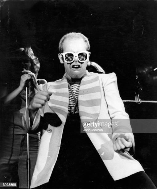 British pop singer Elton John dancing on stage during a concert