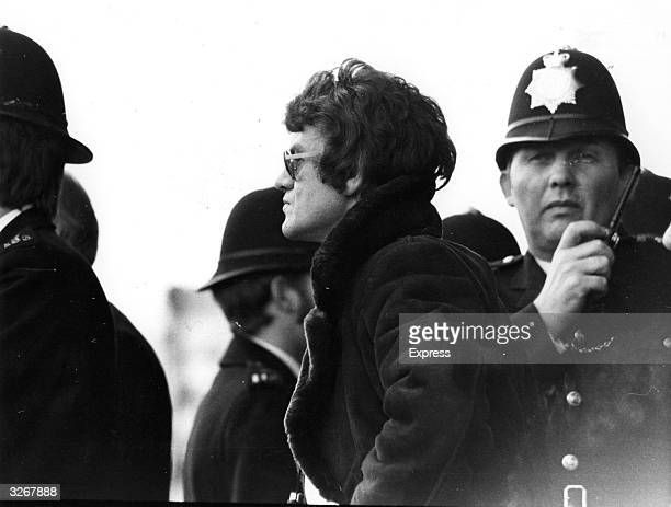 Chelsea Football Club manager Eddie McCreadie is surrounded by police after the match against Hull City was suspended when fans invaded the pitch.