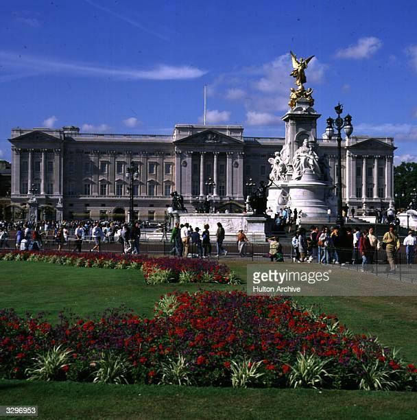Tourists gather outside the railings to Buckingham Palace the London Royal residence