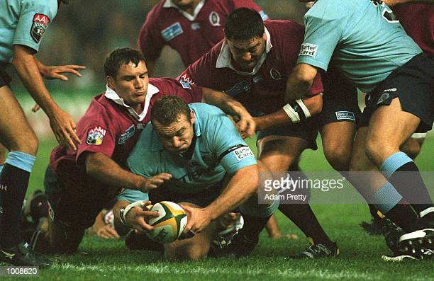 Front row Richard Harry of the NSW Waratah is tackled by QLD forwards during the game QLD Reds v NSW Waratahs at the Sydney Football Stadium Sydney...