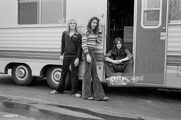 Canadian band Rush posed outside their mobile trailer in Illinois United States during their All the World's a Stage tour in May 1977 Left to right...