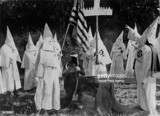 Members of American white supremacist secret society the Ku Klux Klan ceremonially initiate a new recruit at a meeting