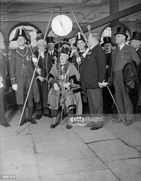 The new Mayor of High Wycombe being weighed as part of a traditional inauguration ceremony He is surrounded by traditionally dressed officials