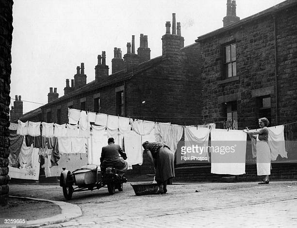 Housewives in Morley, near Leeds, hang their washing across the street, causing problems for a motorcyclist with a sidecar.