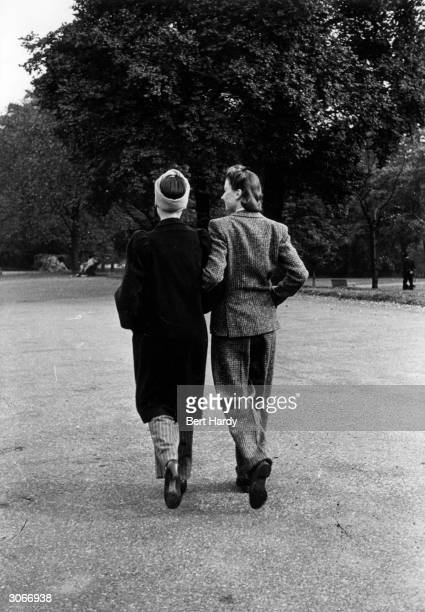 Two women wearing trousers take a stroll in the park during WW II Original Publication Picture Post 910 Should Women Wear Trousers pub 1941