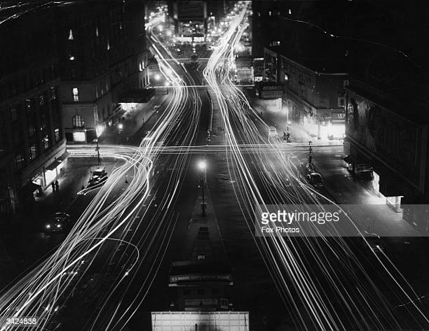 Blurred car headlights illuminating Broadway during a brown out near the end of World War II