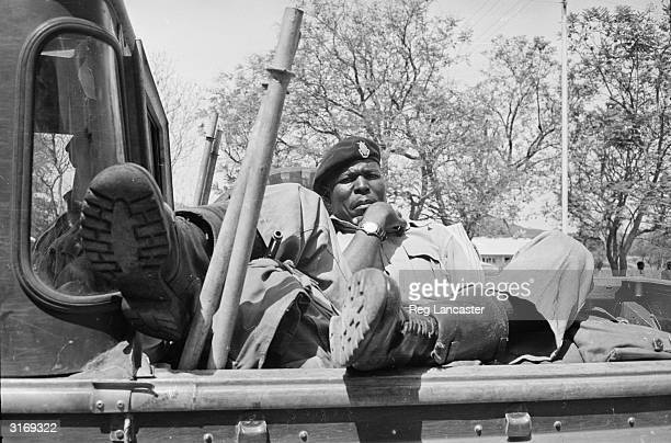 A soldier of the 1st Rhodesian African Rifles sprawls in the back of a truck in Rhodesia