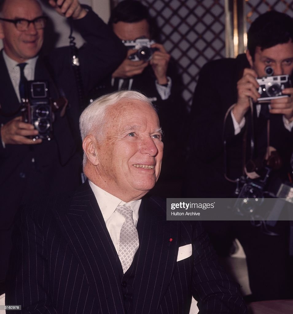 Film star Charlie Chaplin (1889 - 1977) facing press photographers at the Savoy Hotel, London.