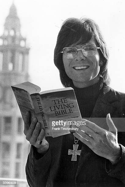 English pop singer Cliff Richard , a convert to Christianity, with a cross round his neck reading a copy of The Living Bible.