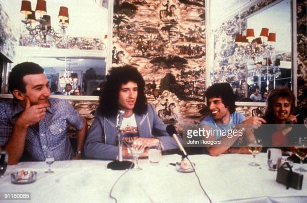 Photo of QUEEN Group portrait at dinner table LR John Deacon Brian May Freddie Mercury and Roger Taylor